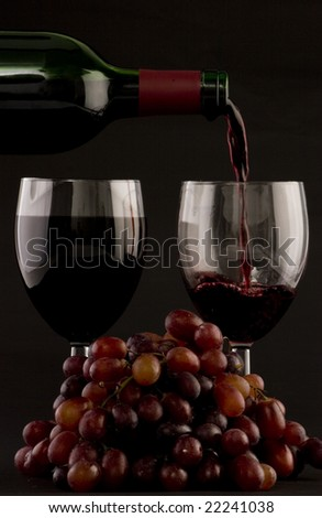 Two glasses of red wine being poured with grapes on a plain background
