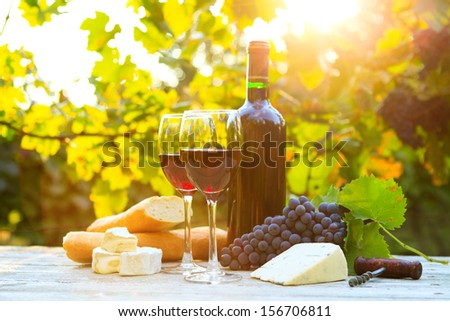 Two glasses of red wine, bottle, cheese and baguette