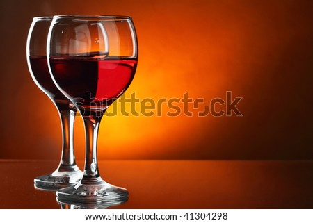 Two glasses of red wine close-up over red background - stock photo