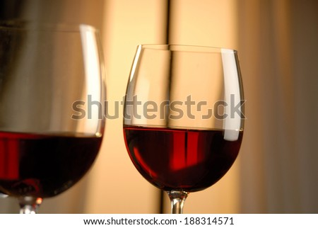 Two glasses of red wine in a romantic setting.