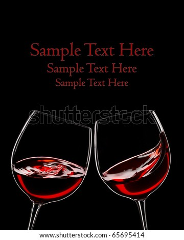 two glasses of red wine, isolated over black, space for copy - stock photo