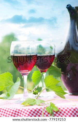 Two glasses of red wine on a picnic table