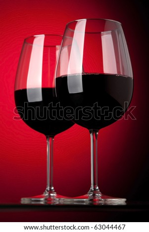 Two glasses of red wine on a red background