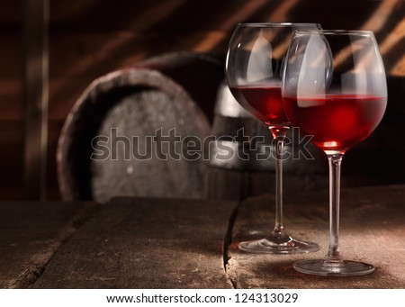 Two glasses of red wine on a table in a vintage beer cellar - stock photo