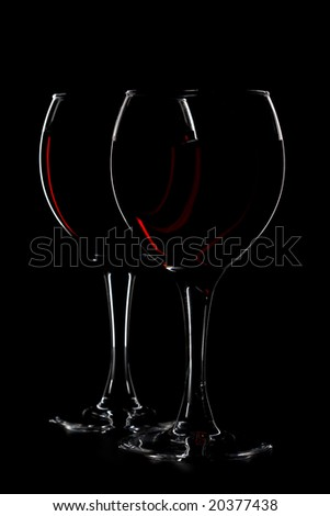 two glasses of red wine on black background - stock photo
