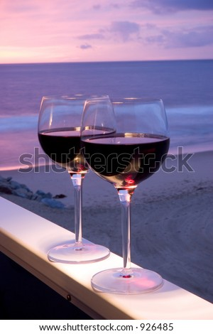 Two glasses of red wine sitting on a ledge over looking the beach, ocean and beautiful sunset.