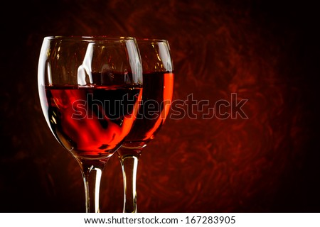 Two glasses of red wine with abstract red background - stock photo