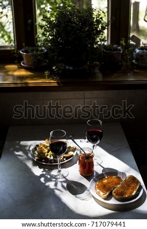 two glasses of red wine with sandwiches with red caviar and bruschettes with cheese and figs. in the kitchen at the window