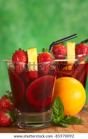 Two glasses of refreshing red wine punch called sangria with orange, apple, mango, garnished with strawberries and pineapple on skewer (Selective Focus, Focus on the fruits on skewer of first drink) - stock photo