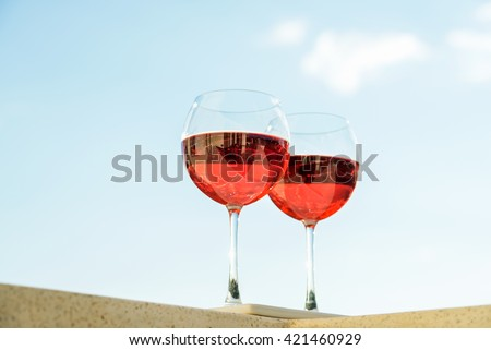 Two glasses of rose wine, blue sky background - stock photo