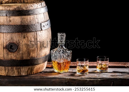 Two glasses of Scotch and old wooden barrel - stock photo