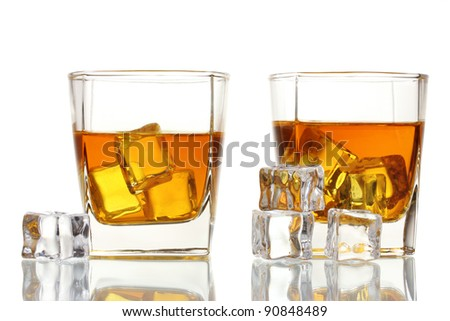 two glasses of scotch whiskey and ice isolated on white