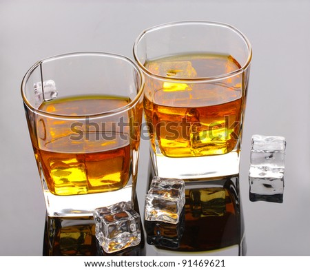 two glasses of scotch whiskey and ice on grey table