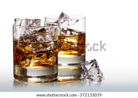 Two glasses of scotch whiskey with ice cubes, background fades to white, copy space - stock photo