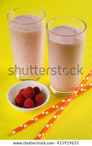 Two glasses of smoothie. Yogurt and raspberries. Dietary smoothies. Fresh raspberries. The swizzle stick. Yellow background.