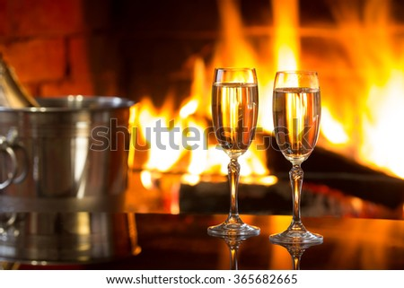 Two glasses of sparkling white wine and ice bucket  in front of warm fireplace. Romantic, cozy relaxed magical atmosphere near fire.   - stock photo