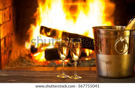 Two glasses of sparkling white wine and ice bucket  in front of warm fireplace. Romantic, cozy relaxed magical atmosphere near fire. Valentines day concept - stock photo