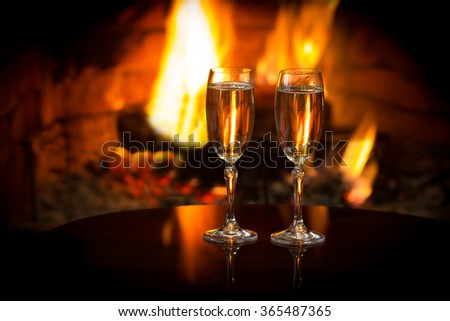 Two glasses of sparkling white wine in front of warm fireplace. Romantic, cozy relaxed magical atmosphere near fire.  - stock photo