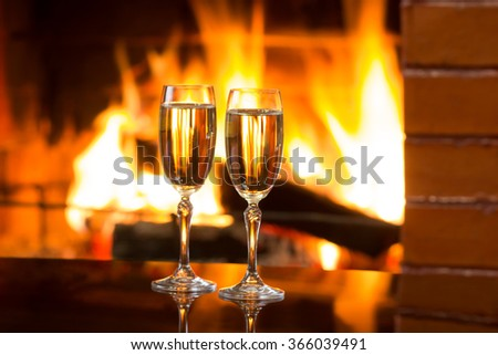 Two glasses of sparkling white wine in front of warm fireplace. Romantic, cozy relaxed magical atmosphere near fire. Valentines day concept - stock photo
