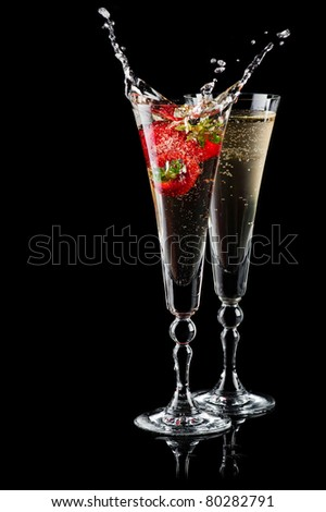 Two glasses of sparkling wine (champagne) with splash and strawberry on black - stock photo