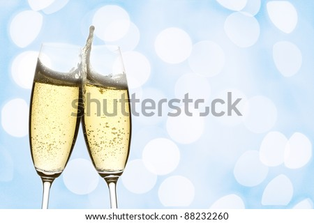 two glasses of sparkling wine with abstract lights, over blue background - stock photo
