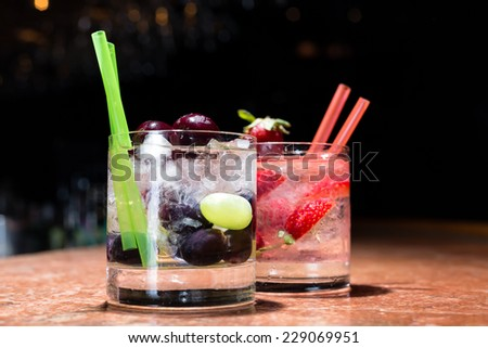 Two glasses of strawberry and grape mojitoes on marble table - stock photo