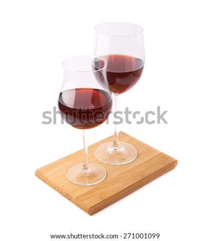Two glasses of the red wine over the serving wooden boards, composition isolated over the white background - stock photo