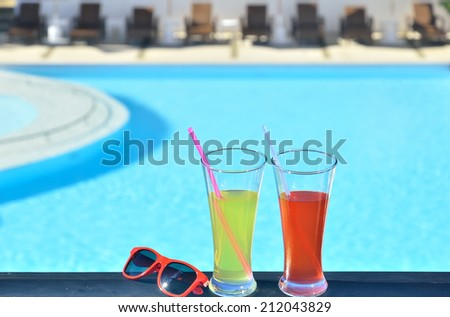 Two glasses of tropical fruit juice and sunglasses beside resorts blue pool - stock photo