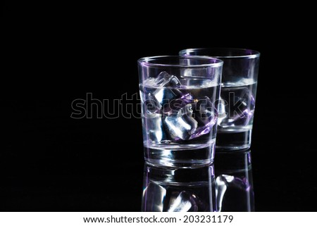 Two glasses of vodka with ice cubes - stock photo
