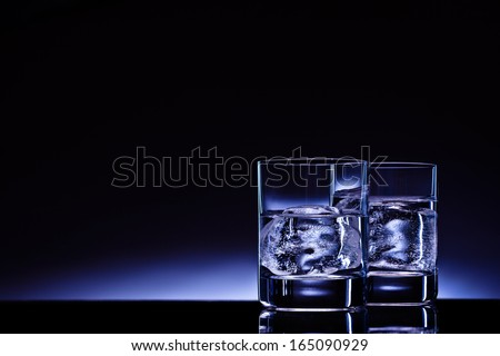 Two glasses of vodka with ice cubes against the background of deep blue glow. - stock photo