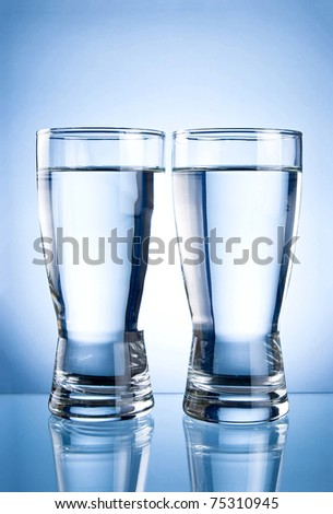 Two glasses of water on a blue background - stock photo