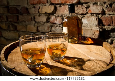 Two glasses of whiskey and the bottle - stock photo