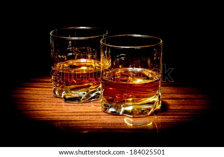 Two glasses of whiskey isolated on black - stock photo