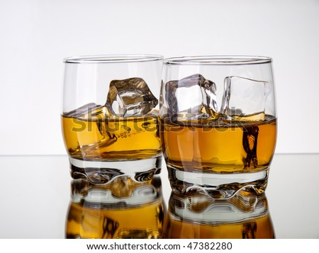 Two glasses of whiskey on a reflective surface - stock photo