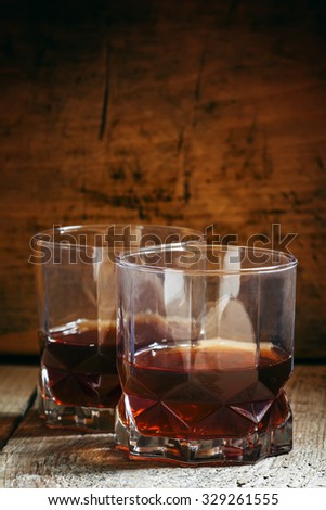 Two glasses of whiskey on dark old wooden background, selective focus
