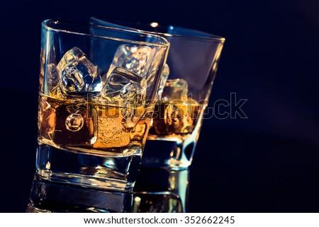 two glasses of whiskey with ice cubes on black background with light tint blue and reflection, time of relax with whisky - stock photo