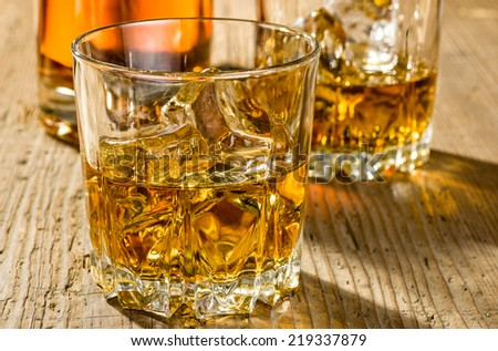 Two glasses of whisky and a bottle - stock photo