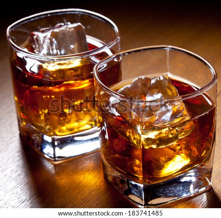 two glasses of whisky with ice - stock photo