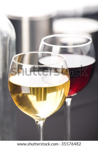 Two glasses of white and red whine.  Grey background - stock photo