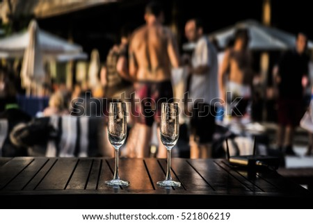two glasses of white or red vine against group of people. Hot beach party. Sexy people. focus on empty glass