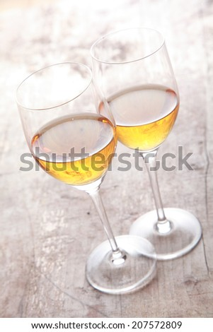 Two glasses of white sherry wine standing touching viewed high angle on a rustic wooden garden table in sunlight