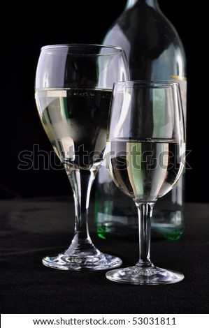 Two glasses of white wine and a bottle in exhibition - stock photo