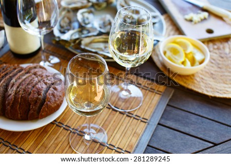 Two glasses of white wine and a bottle on the table. - stock photo
