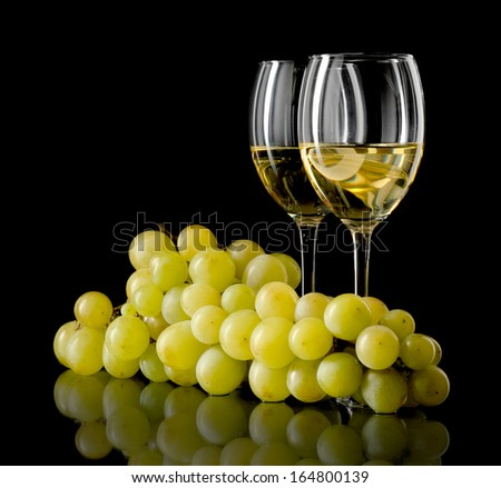 Two glasses of white wine and a bunch of grapes isolated on black - stock photo