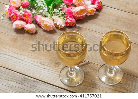 Two glasses of white wine and flowers, closeup