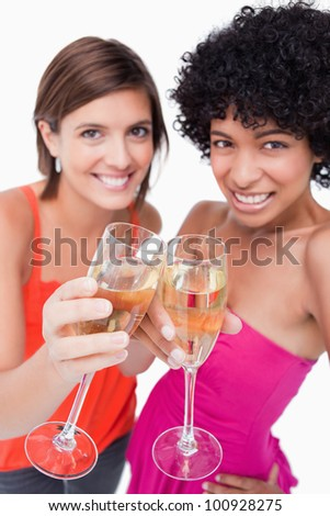 Two glasses of white wine being clinked by young women - stock photo