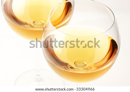 Two glasses of white wine close-up on white background. - stock photo