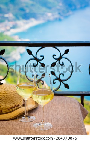 Two glasses of white wine on a table for a luxury restaurant on the Amalfi Coast, terrace panorama, - stock photo