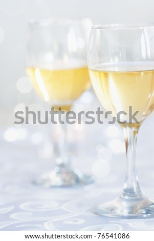 Two glasses of white wine on festive tablecloth - stock photo