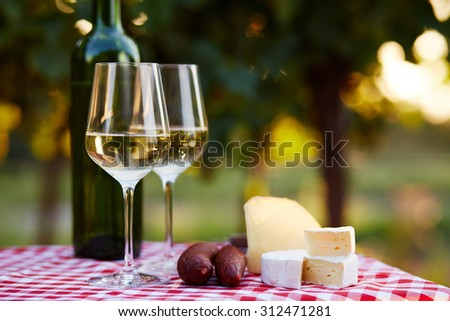 Two glasses of white wine with food on table
